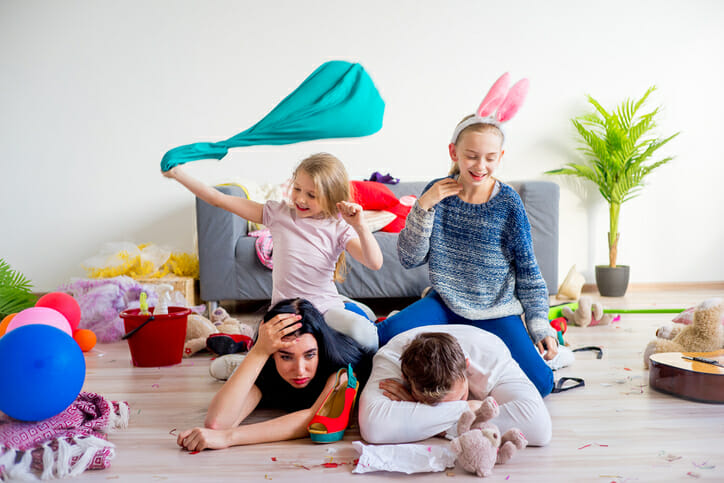 parents on the floor with lots of toys all around them in the living room